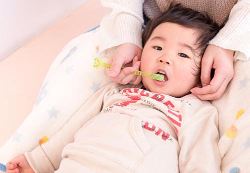 歯磨きしてもらっている赤ちゃん
